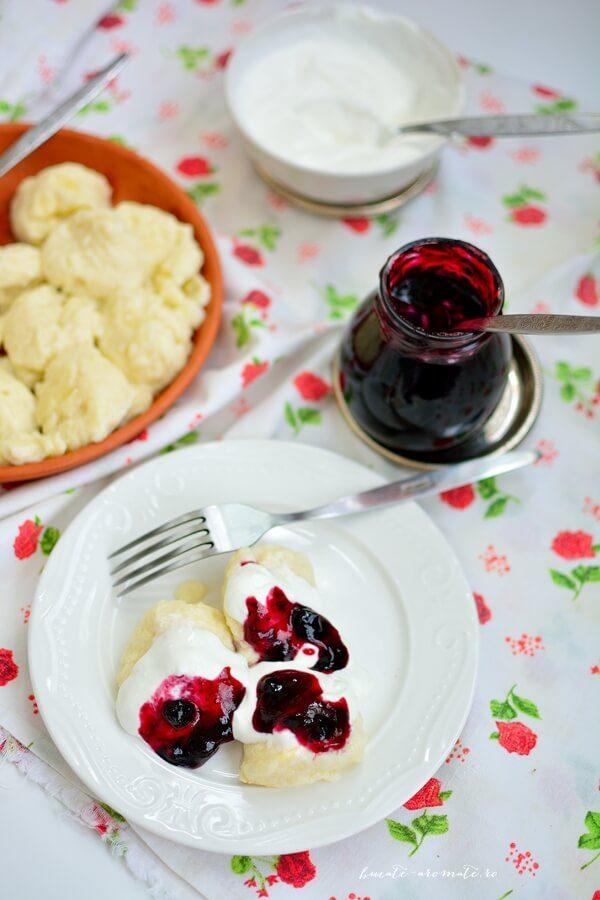 Papanași fierți cu brânză de vaci, serviți cu smântână și dulceață